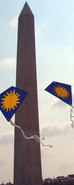 The Washington Monument flanked by two kites in an arch
